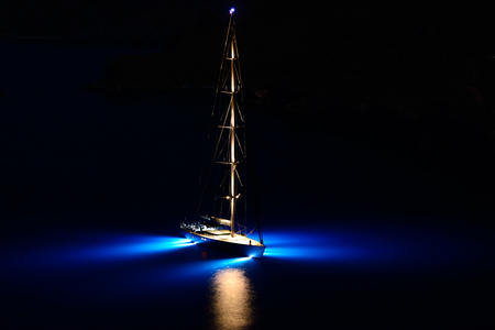 kyklades: Illuminated sailing boat at night with flood lights on, anchored offshore at night Stock Photo