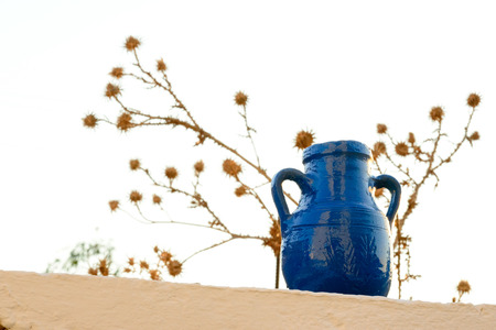 kyklades: Belly amphora painted blue on a limewashed stone wall at a Greek Cyclades Island