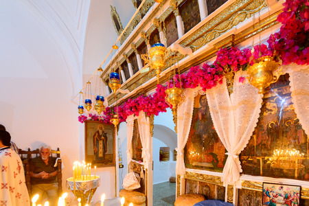 iconostasis: KYTHNOS, GREECE - AUGUST 14, 2014: Decorated iconostasis (templon) of the church of Panagia Stratolatissa, with needleloom embroidery and bougainvillea flowers