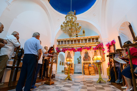 commence: KYTHNOS, GREECE - AUGUST 14, 2014: People waiting for the Assumption liturgy to commence at the church of Panagia Stratolatissa