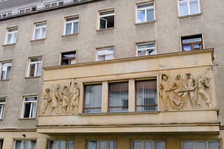 toiling: BRATISLAVA, SLOVAKIA - JULY 7, 2009: Communist era relief of architects planning on the left and workers toiling on the right, on a building facade at Ursulinska street