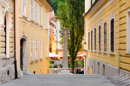 roman pillar: LJUBLJANA, SLOVENIA - JULY 9, 2009: Gledaliska stolba street with its theatrical Roman column and Ljubljanica river in the background