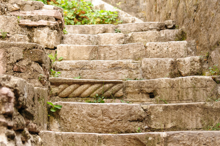 mismatch: Staircase made of stone with one of the steps made using a piece of medieval architectural element of unknown origin in the old town of Kotor