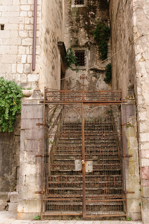 elaborate: Elaborate handmade iron gate that is rusting away in the old town of Kotor, Montenegro Stock Photo