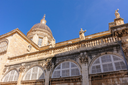 adorning: Assumption of Virgin Mary cathedral with semicircular windows and statues of saints adorning the roof