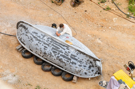 sander: DUBROVNIK, CROATIA - AUGUST 31, 2009: Technician using an electrical sander to sand down the hull of a boat