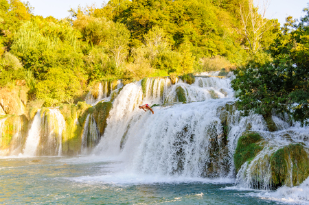 september 2: KRKA NATIONAL PARK, CROATIA - SEPTEMBER 2, 2009: Man caught mid-air diving off the Skradinski Buk waterfalls into the Krka river.