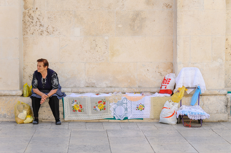 exhibiting: SIBENIK, CROATIA - SEPTEMBER 2, 2009: Local resident as a street peddler exhibiting her handicraft embroidery on the side of St. James cathedral