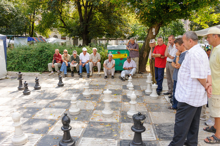 preoccupied: SARAJEVO, BOSNIA AND HERZEGOVINA - SEPTEMBER 4, 2009: Senior men preoccupied with an outdoor giant chess game
