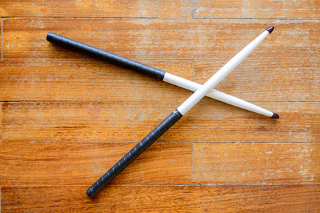 drumsticks: Size 5A hickory drumsticks painted white with black teardrop shaped tips and wrapped with tennis overgrip tape.