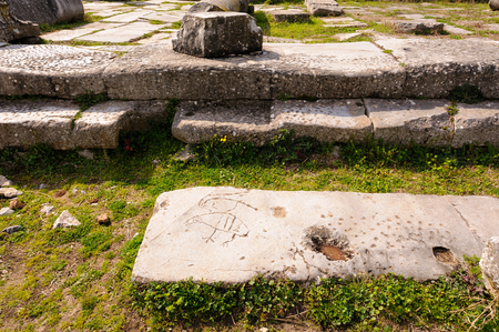 inscribed: KRINIDES, GREECE - FEBRUARY 25, 2010: Christian symbol or childrens games inscribed on marble ruins at Philippi