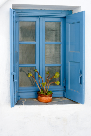 greek pot: Typical blue wooden window with shutters at an Aegean Islander whitewashed house. Archivio Fotografico