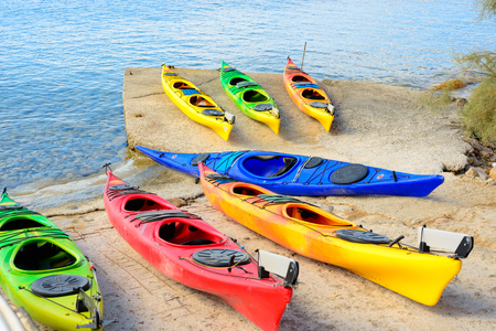 kyklades: Multi-colored plastic kayaks arranged on a cement pier ready to be taken out on the water.