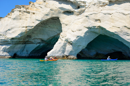 kyklades: MELOS, GREECE - SEPTEMBER 4, 2012: People with kayaks exploring the Blue Cave at Kleftiko, at the southwest coastline of Melos island.