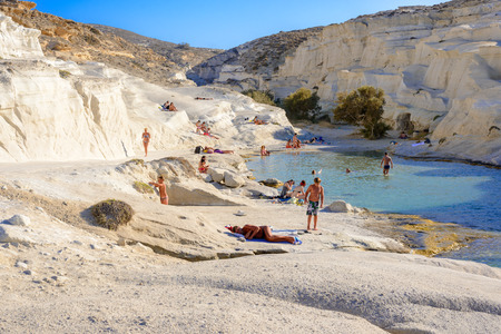 kyklades: MELOS, GREECE - SEPTEMBER 4, 2012: Sarakiniko cove, beach and gorge with people sunbathing and swimming. Editorial