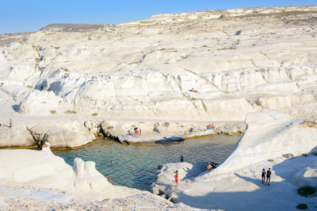 kyklades: MELOS, GREECE - SEPTEMBER 4, 2012: Sarakiniko cove with people sunbathing and swimming.