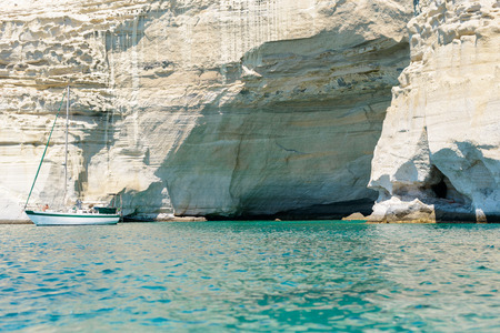 kyklades: MELOS, GREECE - SEPTEMBER 4, 2012: A sailing boat anchored off a cave at Kleftiko. The caves and rock formations were used by pirates for hideouts. Editorial