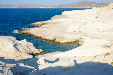 kyklades: Sarakiniko, Melos, Greece. Complex shapes and gullies formed by water flowing into the gorge and out to sea between soft white rocks has carved out the stream bed into a moonscape. Stock Photo