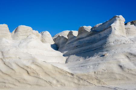Sarakiniko, Melos, Greece. Complex shapes and gullies formed by water flowing into the gorge and out to sea between soft white rocks has carved out the stream bed into a moonscape. Stock Photo