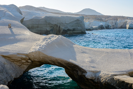 gully: Sarakiniko, Melos, Greece. Complex shapes and gullies formed by water flowing into the gorge and out to sea between soft white rocks has carved out the stream bed into a moonscape. Stock Photo