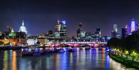London skyline at night with lights reflecting from the Thames River photo