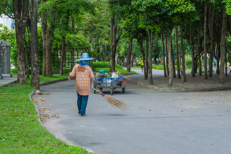 An Asian woman is sweeping dry leaves by the road in the outdoor garden. Cleaning concept. Redakční