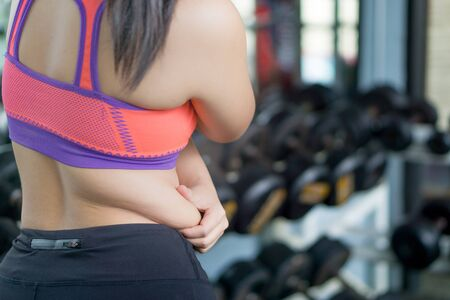 Close up woman holding excessive fat belly at fitness gym. Diet, weight loss, slim body, healthy lifestyle concept.
