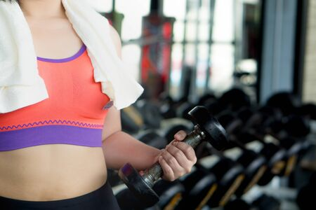 Young woman stands holding dumbbell at fitness gym. Diet, weight loss, slim body, healthy lifestyle concept.