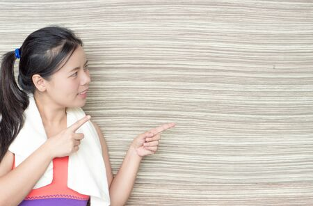 Young woman standing and pointing finger at copy space wooden background at fitness gym. Shows free space for your promotional. 版權商用圖片