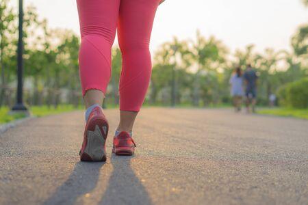 Scarpa del primo piano. Gambe femminili che fanno jogging e camminano al parco. Concetto di sport ed esercizio fisico