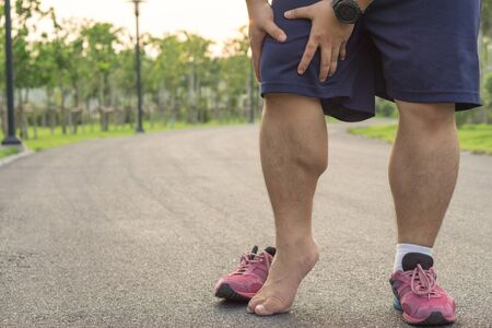 Knee Injuries. Fat man holding knee with his hands in pain after suffering muscle injury during a running workout at park. Healthcare and sport concept.
