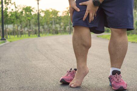 Knieverletzungen. Dicker Mann, der das Knie mit Schmerzen in den Händen hält, nachdem er während eines Lauftrainings im Park Muskelverletzungen erlitten hatte. Gesundheits- und Sportkonzept.
