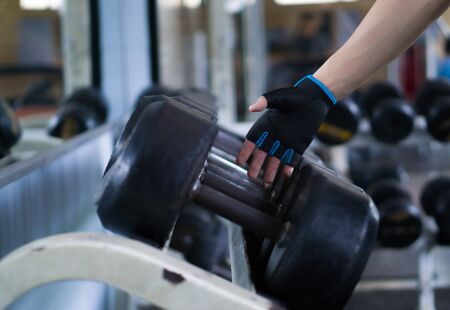 Close up hand taking heavy rusty dumbbell to exercise for strength training. sport, fitness, health, lifestyle and people concept Imagens