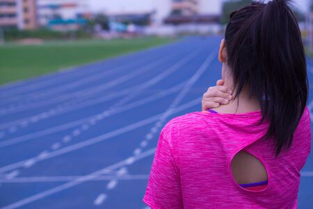 Young asian woman feel pain on her neck and shoulder while running or jogging on running track. Health care and medical concept.