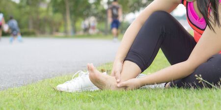 Ankle sprained. Young woman suffering from an ankle injury while jogging and running at the park. Healthcare and sport concept.