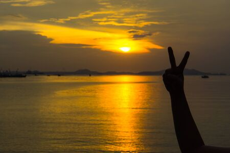 Silhouette of two fingers of womans hand or victory in front of the sun during sunset time. Fighting concept