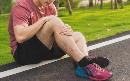 Knee Injuries. Young sport man holding knee with his hands in pain after suffering muscle injury during a running workout at park. Healthcare and sport concept.