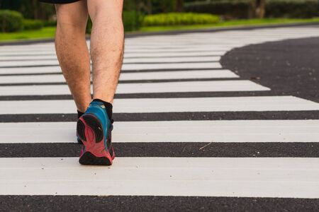 Closeup shoe. Male legs walking on the zebra crossing track. Safety road crossing concept