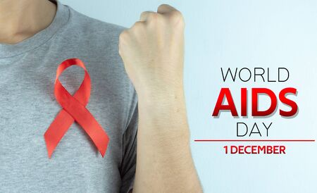 Aids awareness, male hands holding red AIDS awareness ribbon. World Aids Day, Healthcare and medical concept.