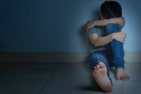 sad man hug his knee and cry sitting alone in a dark room. Depression, unhappy, stressed and anxiety disorder concept