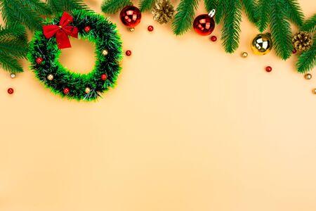 Weihnachtsfeiertagszusammensetzung, Draufsicht auf rote und goldene Weihnachtsdekorationen auf gelbem Hintergrund mit Kopienraum für Text. Flache Lage, Winter, Postkartenvorlage, Konzept des neuen Jahres. Standard-Bild
