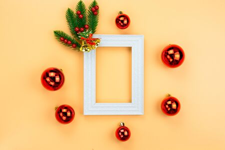 Christmas holidays composition, top view of red Christmas decorations and picture frame on yellow background with copy space for text. Flat lay, winter, postcard template, new year concept.