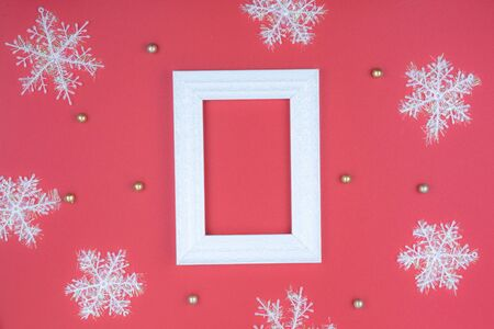 Christmas holidays composition, top view of snowflake decorations and picture frame on red background with copy space for text. Flat lay, winter, postcard template, new year concept.