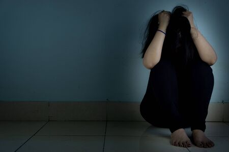 sad woman hug her knee and cry sitting alone in a dark room. Depression, unhappy, stressed and anxiety disorder concept