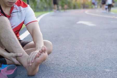 Ankle sprained. Young man suffering from an ankle injury while running at park. Healthcare and sport concept.