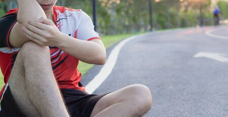A male athlete suffering from arm and elbow pain and injury at the park. Sport and healthcare concept.