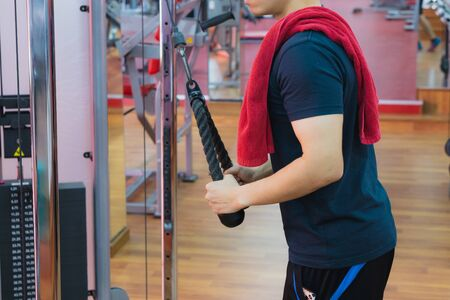 Young sporty man doing rope pulldown in gym. Sport and exercise concept.