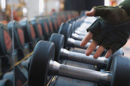 Close up hand taking heavy dumbbell to exercise for strength training. sport, fitness, health, lifestyle and people concept