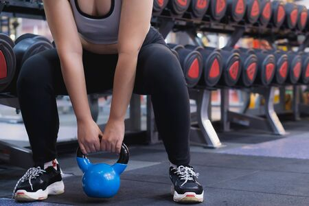 Young sporty woman doing Sumo squats with kettlebell in gym. Sport and exercise concept.