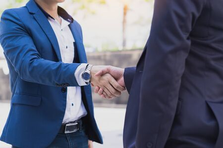 Two business man making handshake in the city. Business etiquette, congratulation, merger and acquisition concepts.